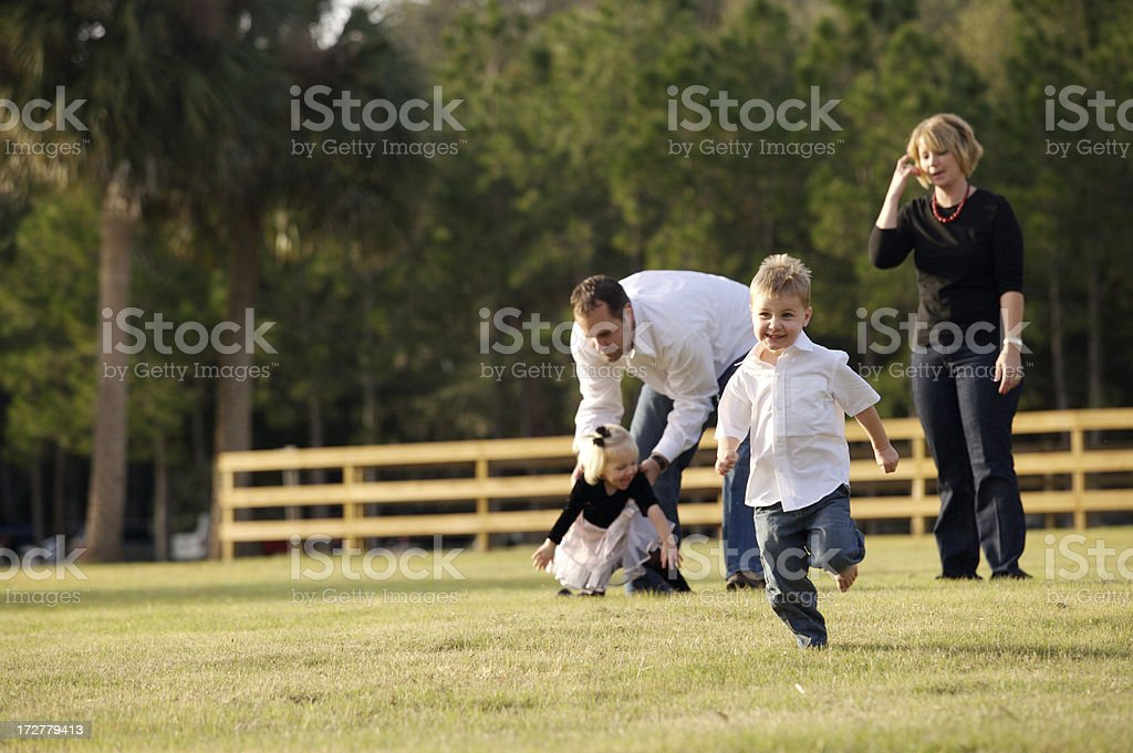 Boy running from parents playing royalty-free stock photo