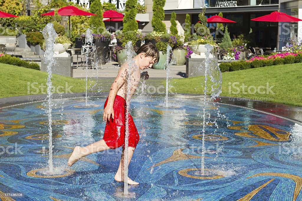 Boy running through water in fountain royalty-free stock photo