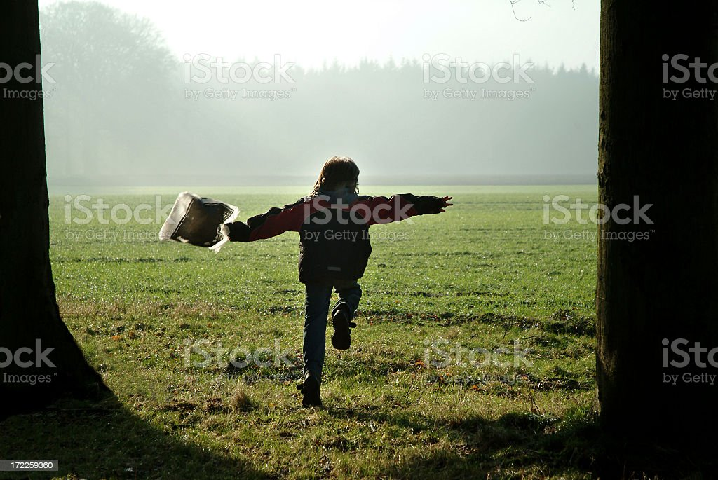 Boy running with plastic bag in between trees royalty-free stock photo