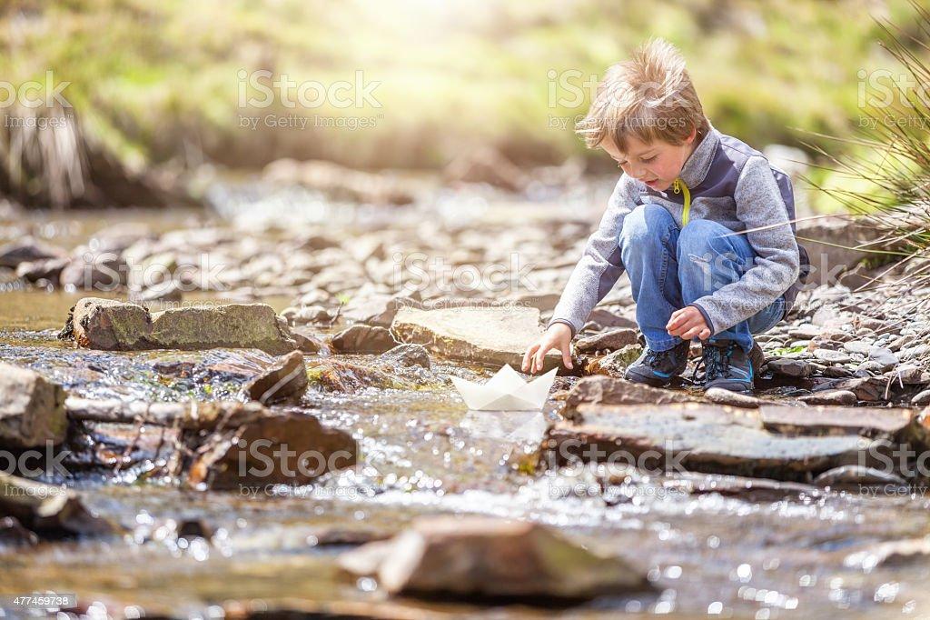 Boy sailing a paper boat stock photo