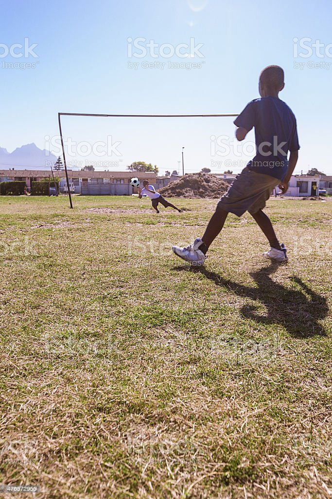 Boy saving a penalty in Gugulethu, Cape Town, South Africa royalty-free stock photo
