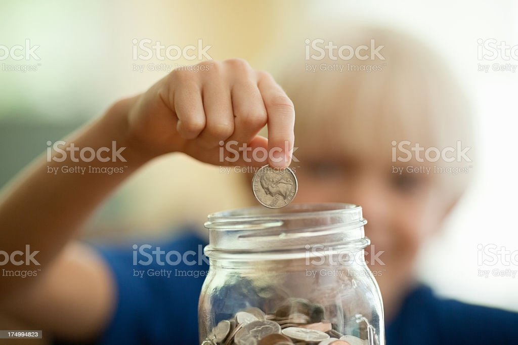 Boy Saving Coins In Money Jar stock photo