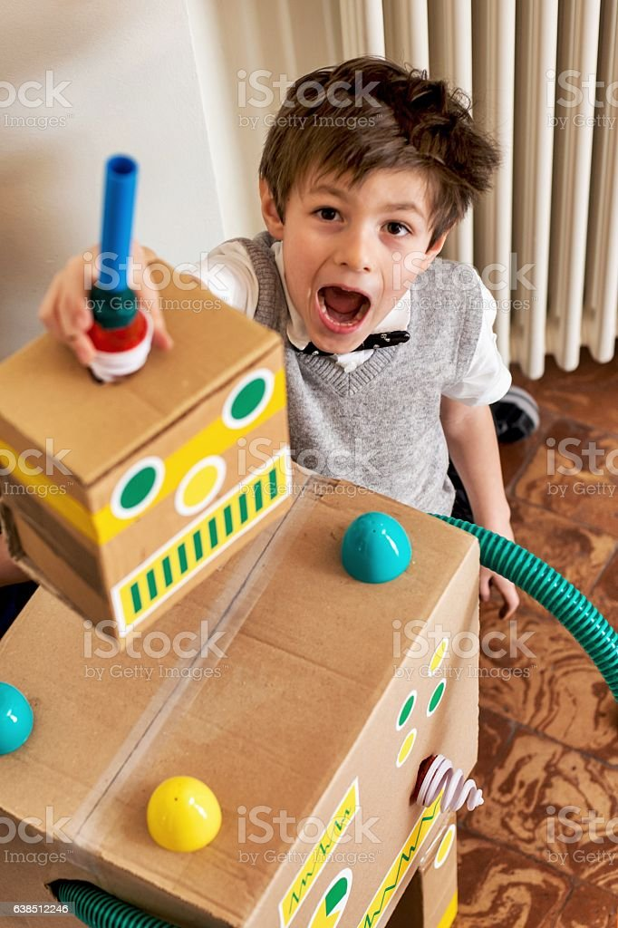 Boy Scienti Playing with His Toy Robot stock photo