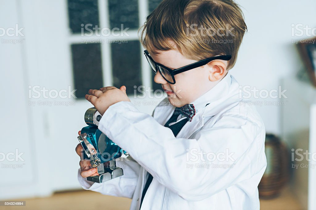 Boy scientist plays with a small toy robot stock photo