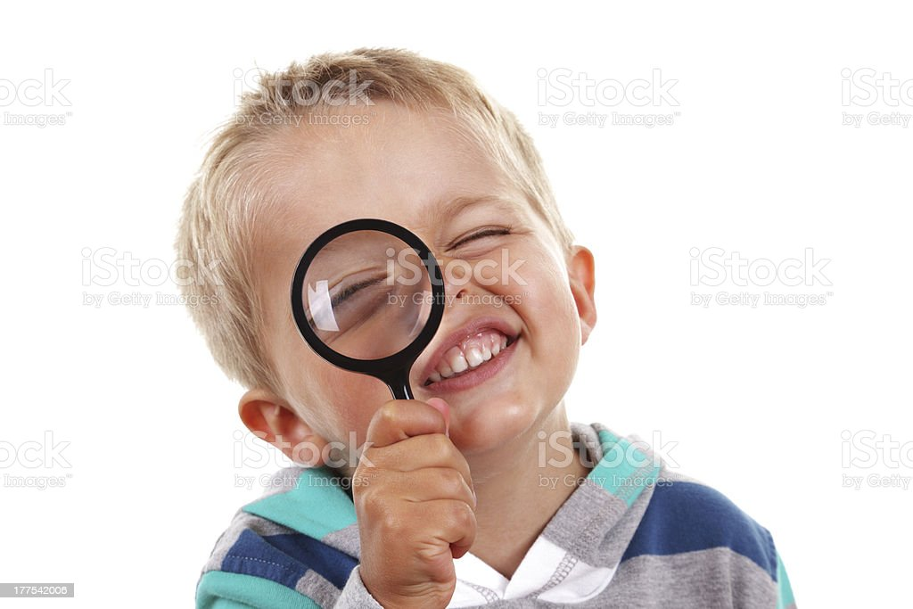 Boy searching with magnifying glass stock photo