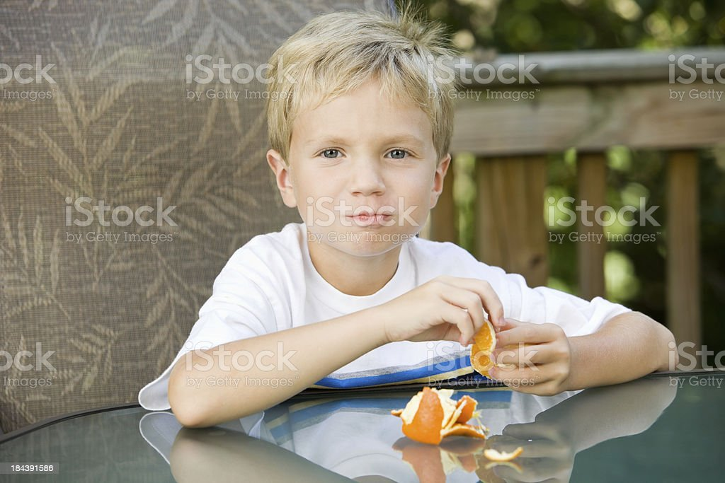 Boy Seated at Glass Top Deck Table Enjoying an Orange stock photo
