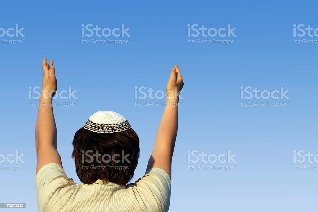 Boy, seen from behind, praying and reaching to the sky stock photo