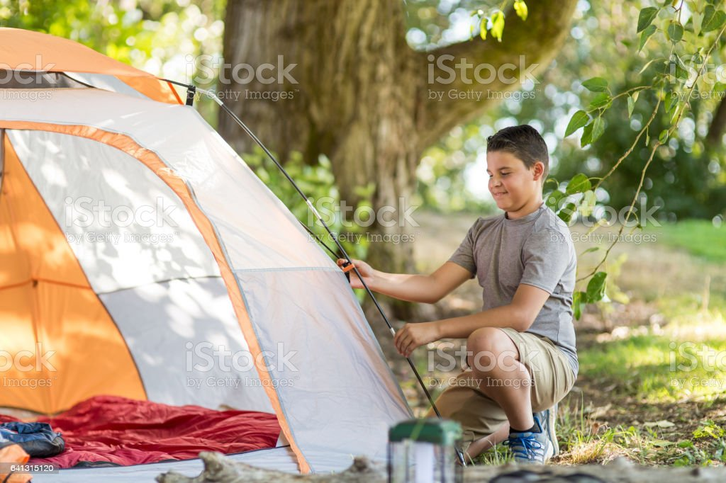 Boy setting up tent stock photo