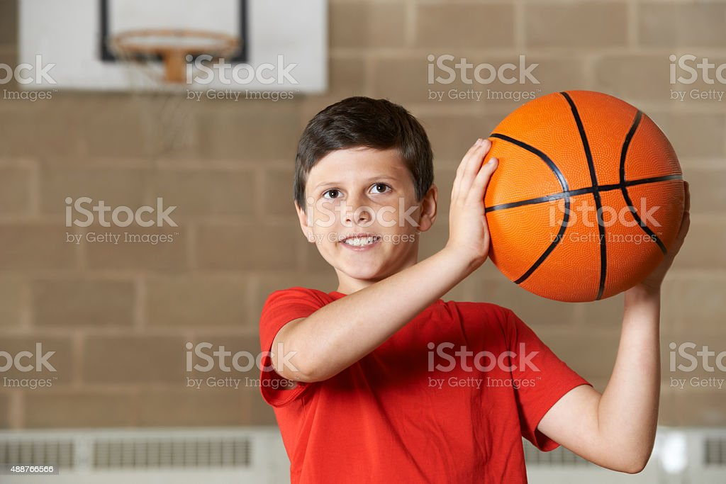 Boy Shooting During Basketball Match In School Gym stock photo