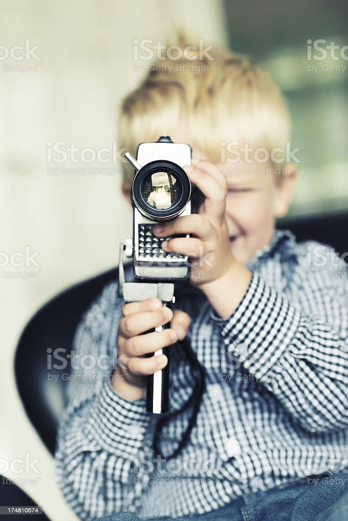 Boy shoots a video with an old retro camera royalty-free stock photo