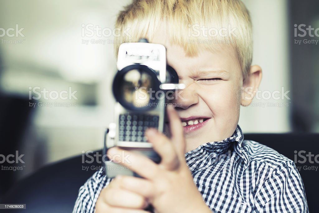 Boy shootsing a video with an old retro cine camera royalty-free stock photo