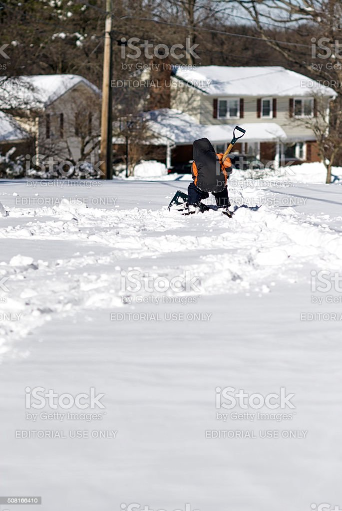 Boy Shovels Show in Street stock photo