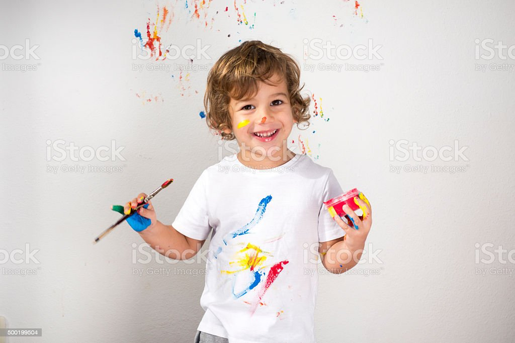 Boy Showing Colorful Paint on His Hands stock photo