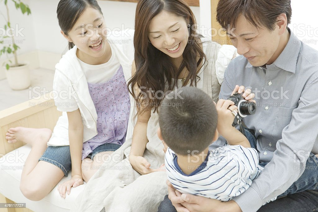 Boy showing parents and elder sister a camera royalty-free stock photo
