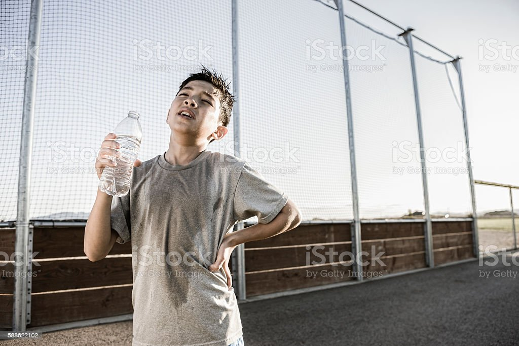 Boy shows exhaustion after practice. stock photo