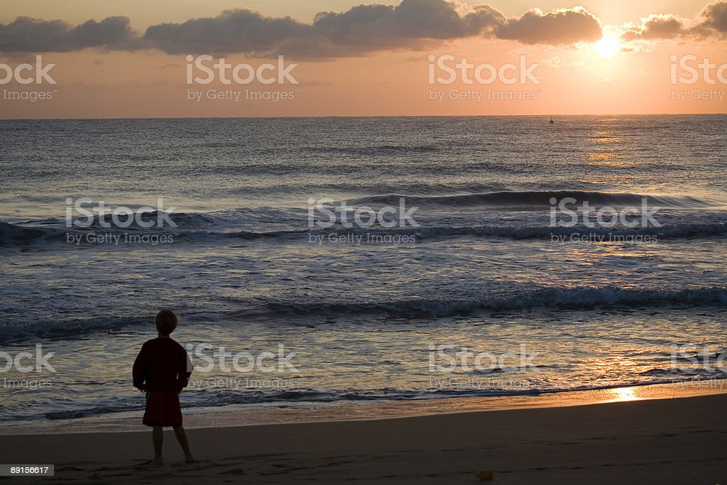 Boy sillouette at sunrise over ocean royalty-free stock photo
