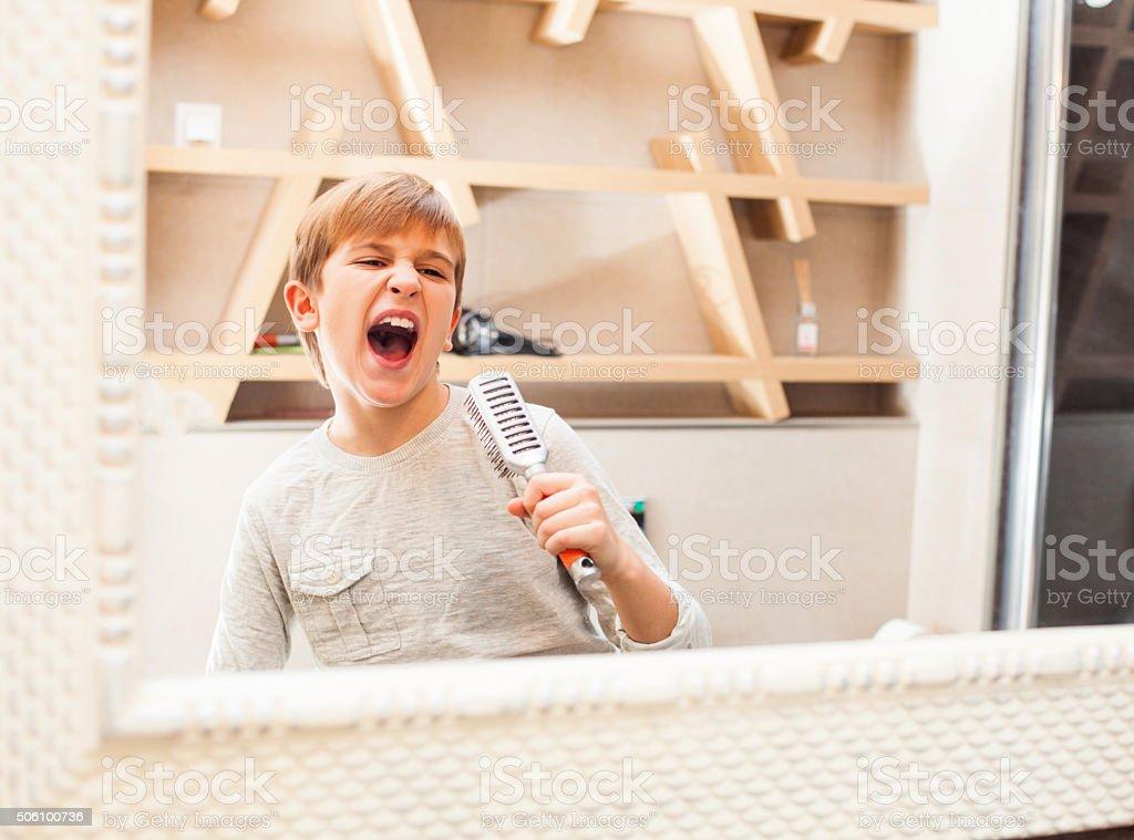 Boy singing into the hairbrush stock photo