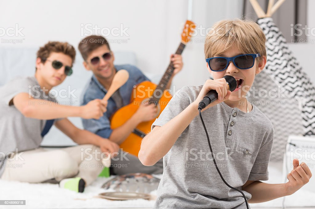 Boy singing to microphone stock photo