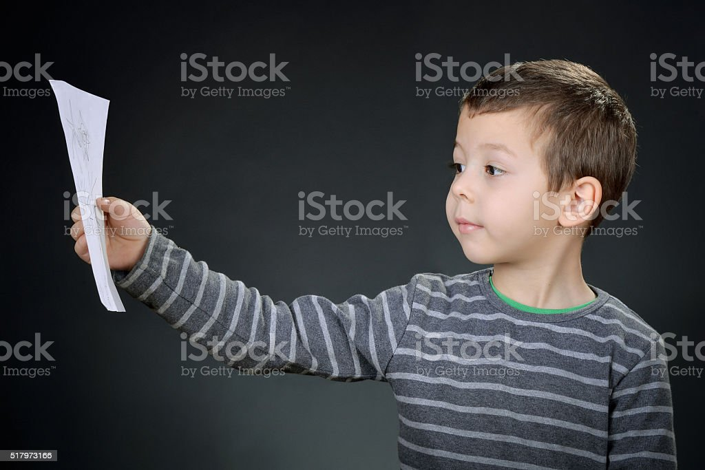 Boy sits and draws studio stock photo