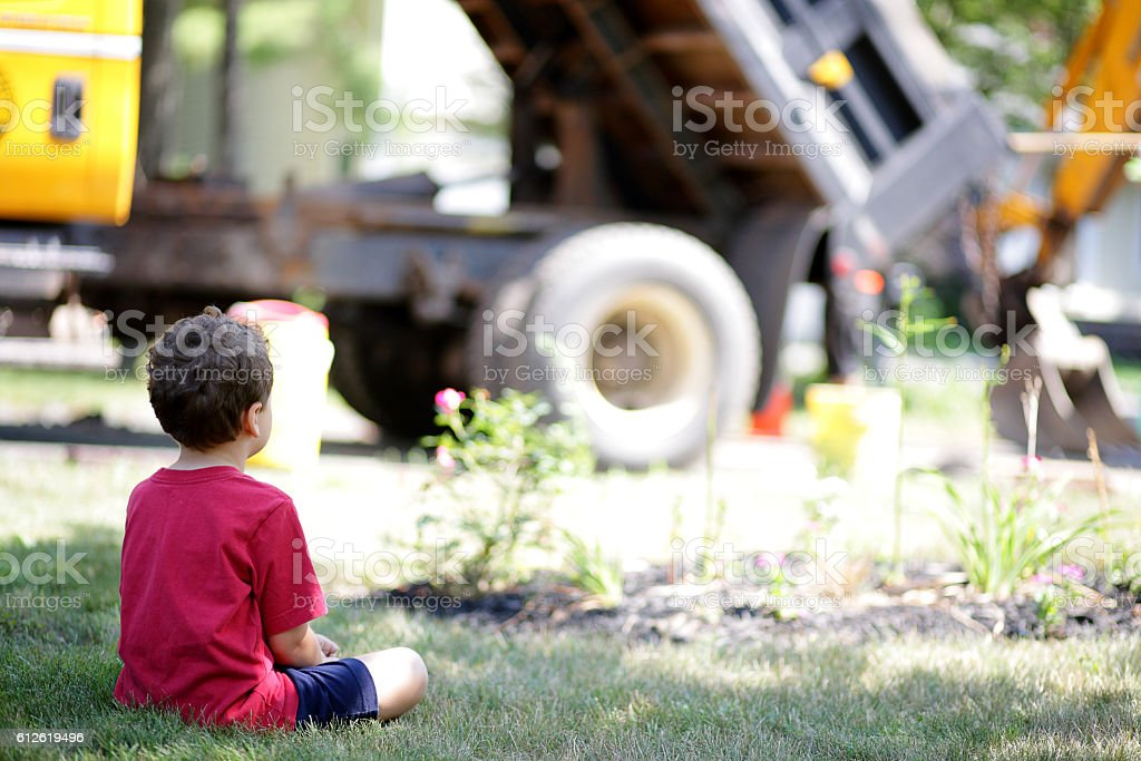 Boy sits and watches roadwork from his front lawn stock photo