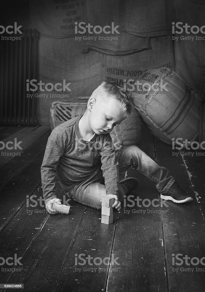 Boy sitting and playing with wooden blocks stock photo