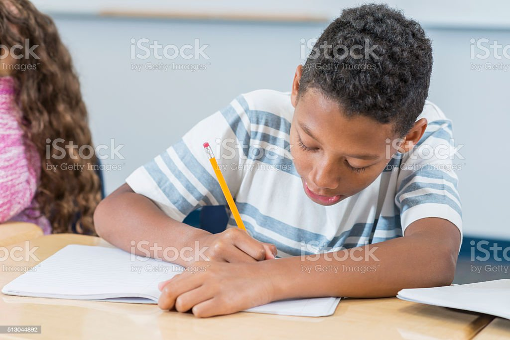 Boy sitting at desk in class writing in notebook stock photo