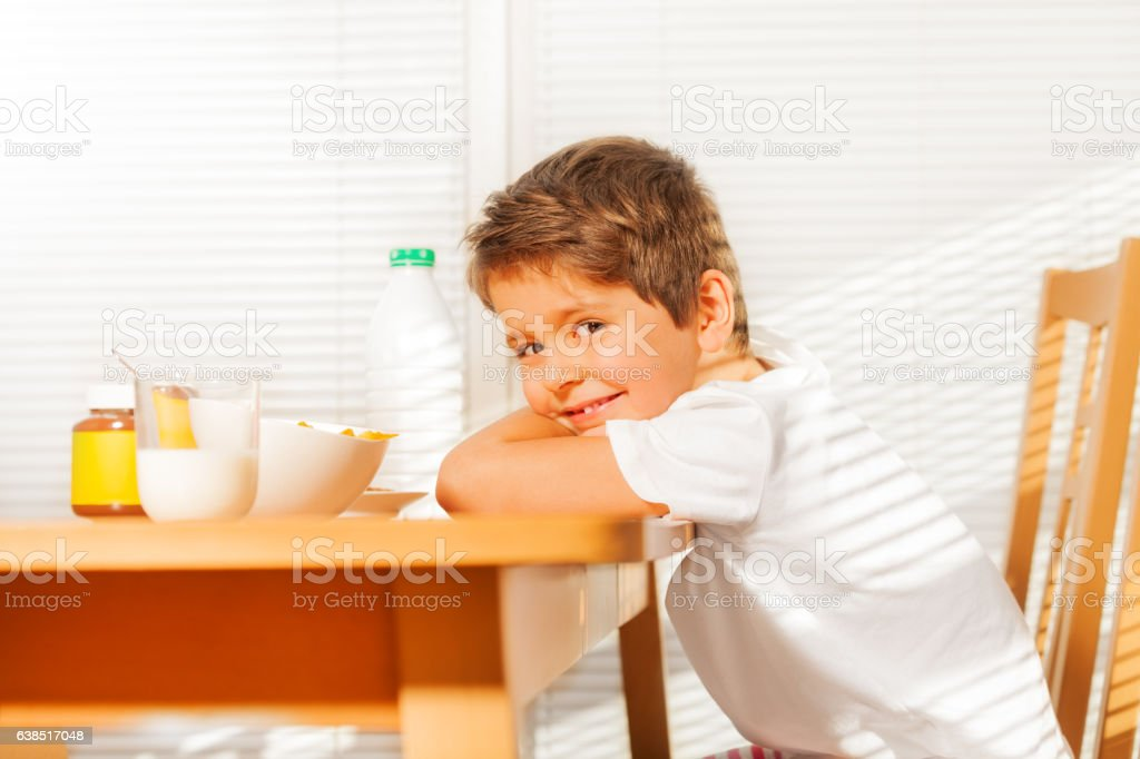 Boy sitting at table during breakfast in kitchen stock photo