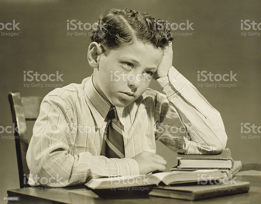 Boy (10-11) sitting at table over open book, head resting on hand, (B&W), close-up stock photo