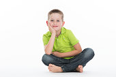 boy sitting cross legged on white