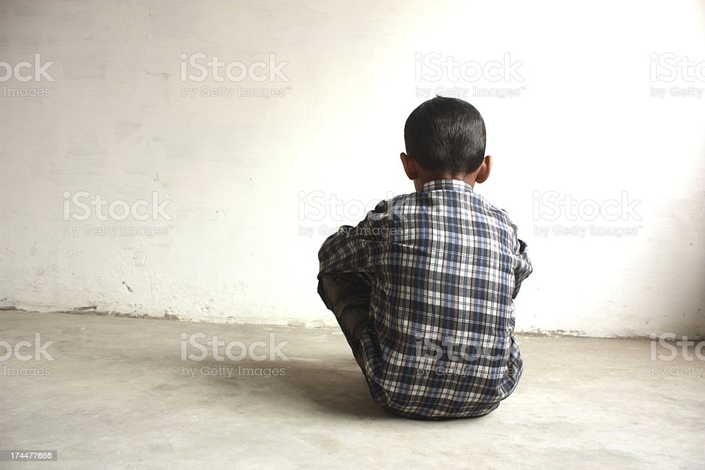 A boy sitting facing a white wall alone  stock photo