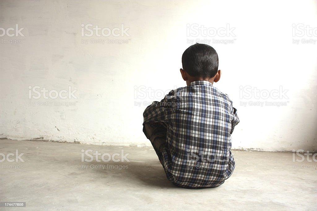 A boy sitting facing a white wall alone  stock photo