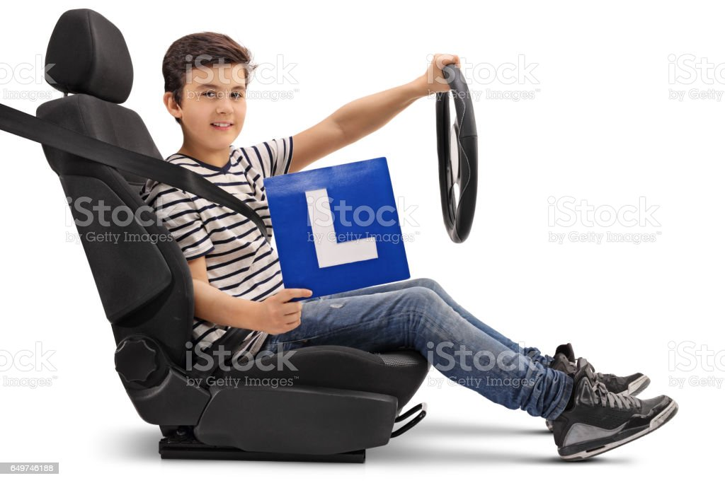 Boy sitting in a car seat and showing an L-sign stock photo