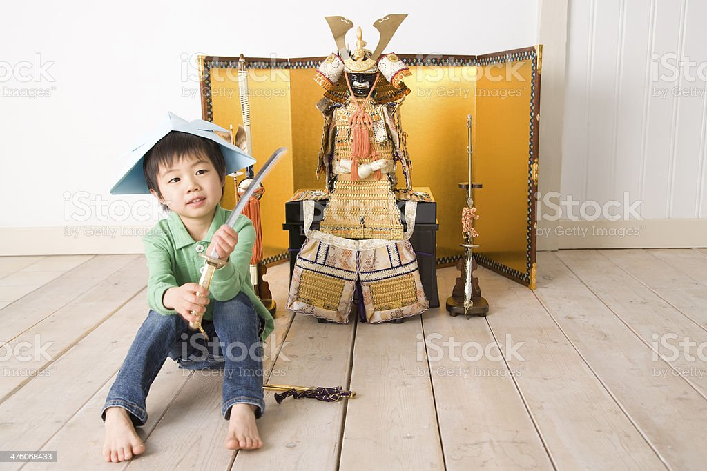 Boy sitting in front of May doll stock photo