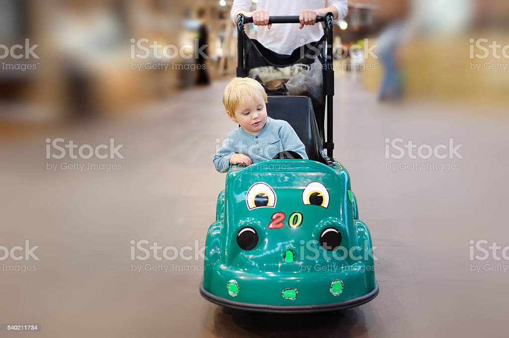 Boy sitting in the shopping cart made as toy car stock photo