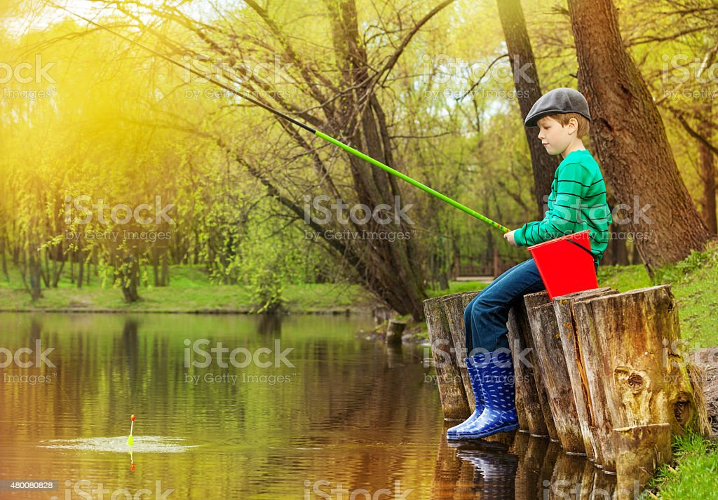 Boy sitting, looking at water and fishing on pond stock photo