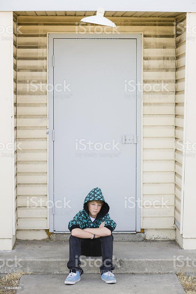 Boy Sitting on a Curb stock photo