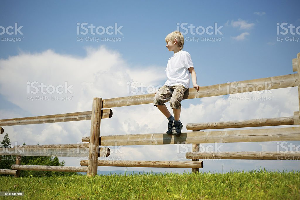 Boy sitting on a fence royalty-free stock photo