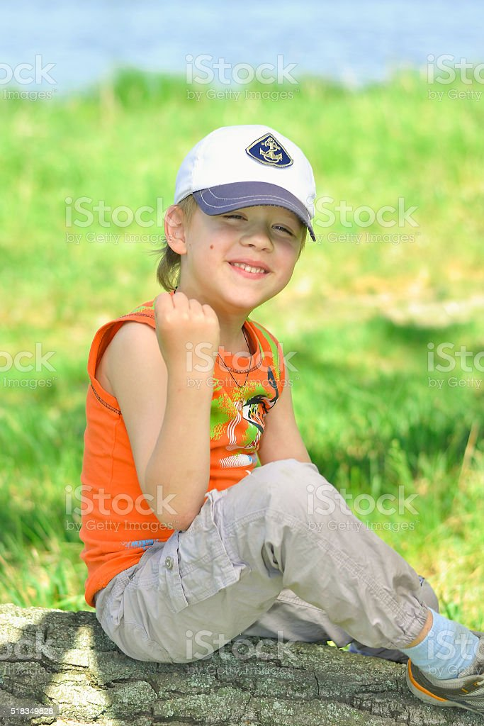 boy sitting on a log in nature stock photo