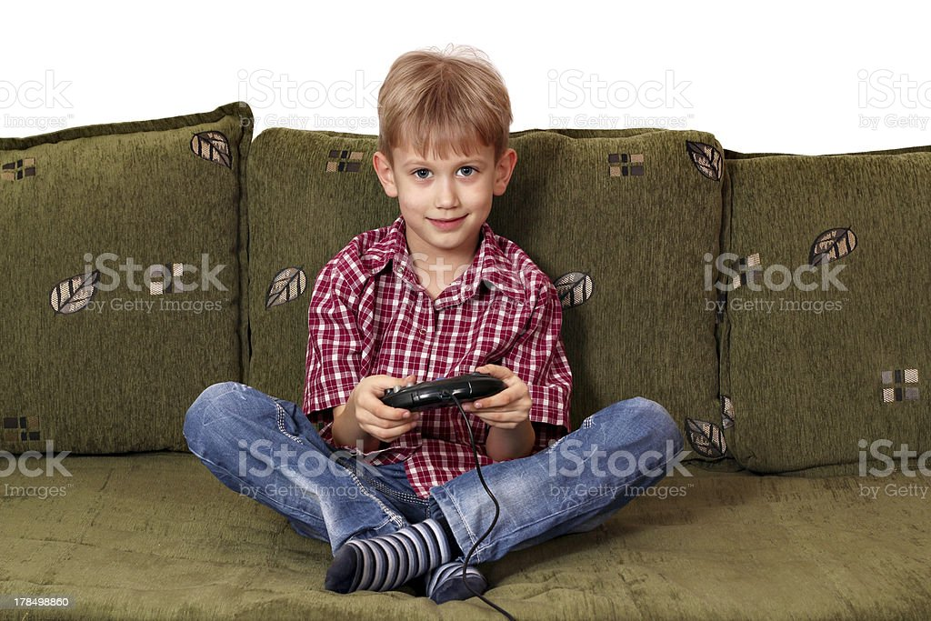 boy sitting on bed and play video game royalty-free stock photo