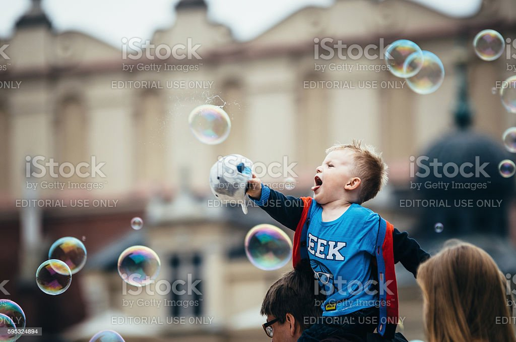 Boy sitting on dad's shoulders and touched giant bubbles стоковое фото
