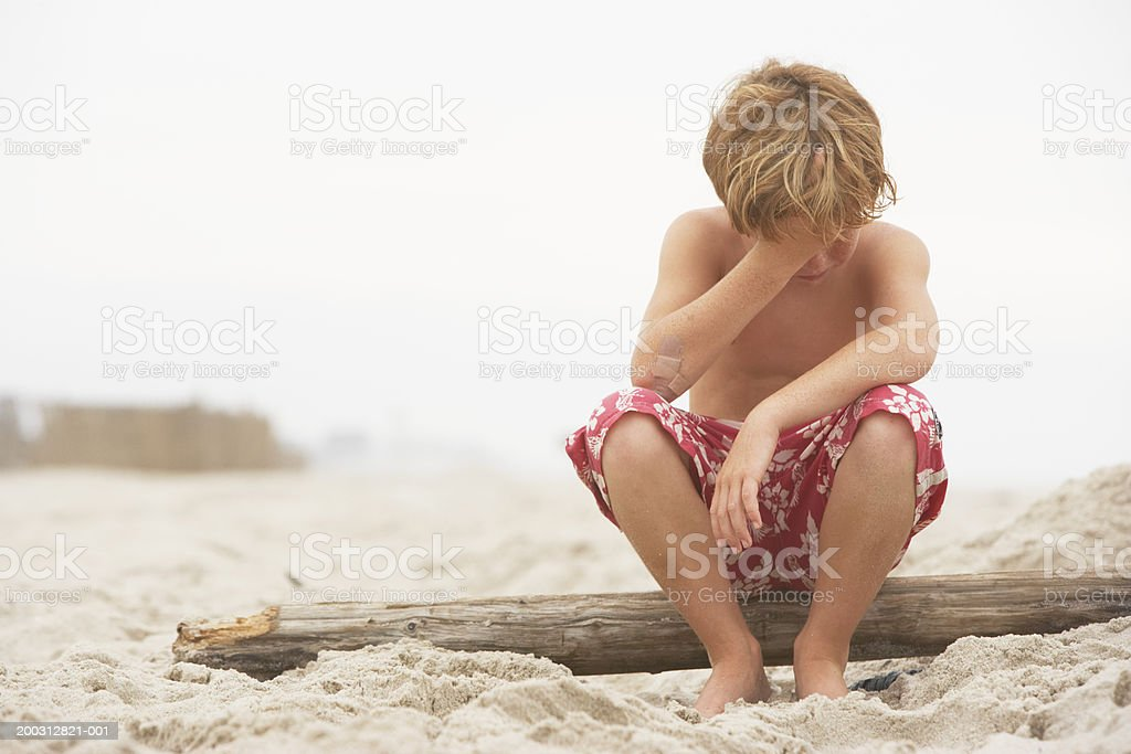 Boy (6-8) sitting on driftwood on beach, hand to head royalty-free stock photo