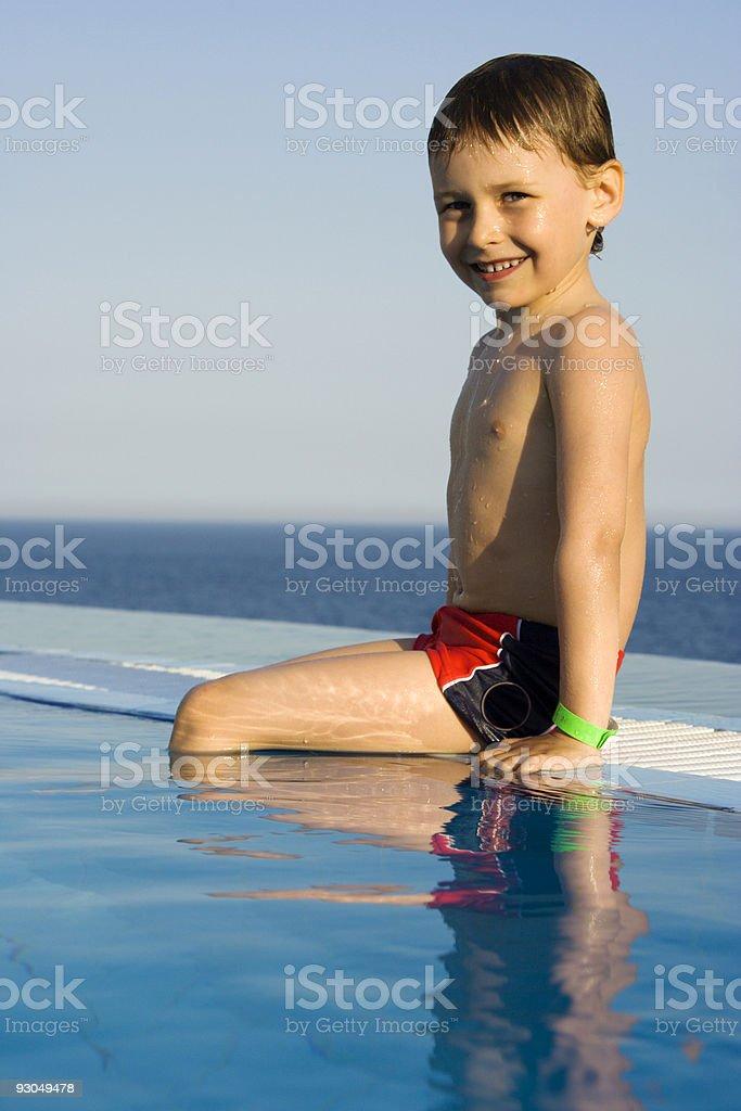 Boy sitting on edge of infinity pool royalty-free stock photo