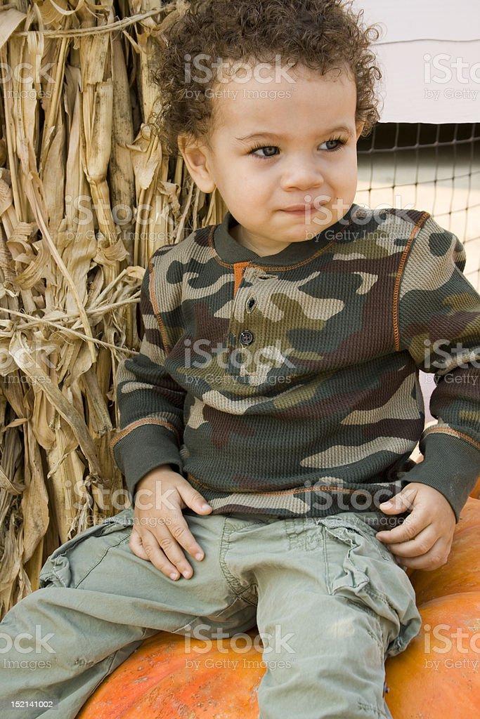 Boy Sitting on Pumpkin stock photo