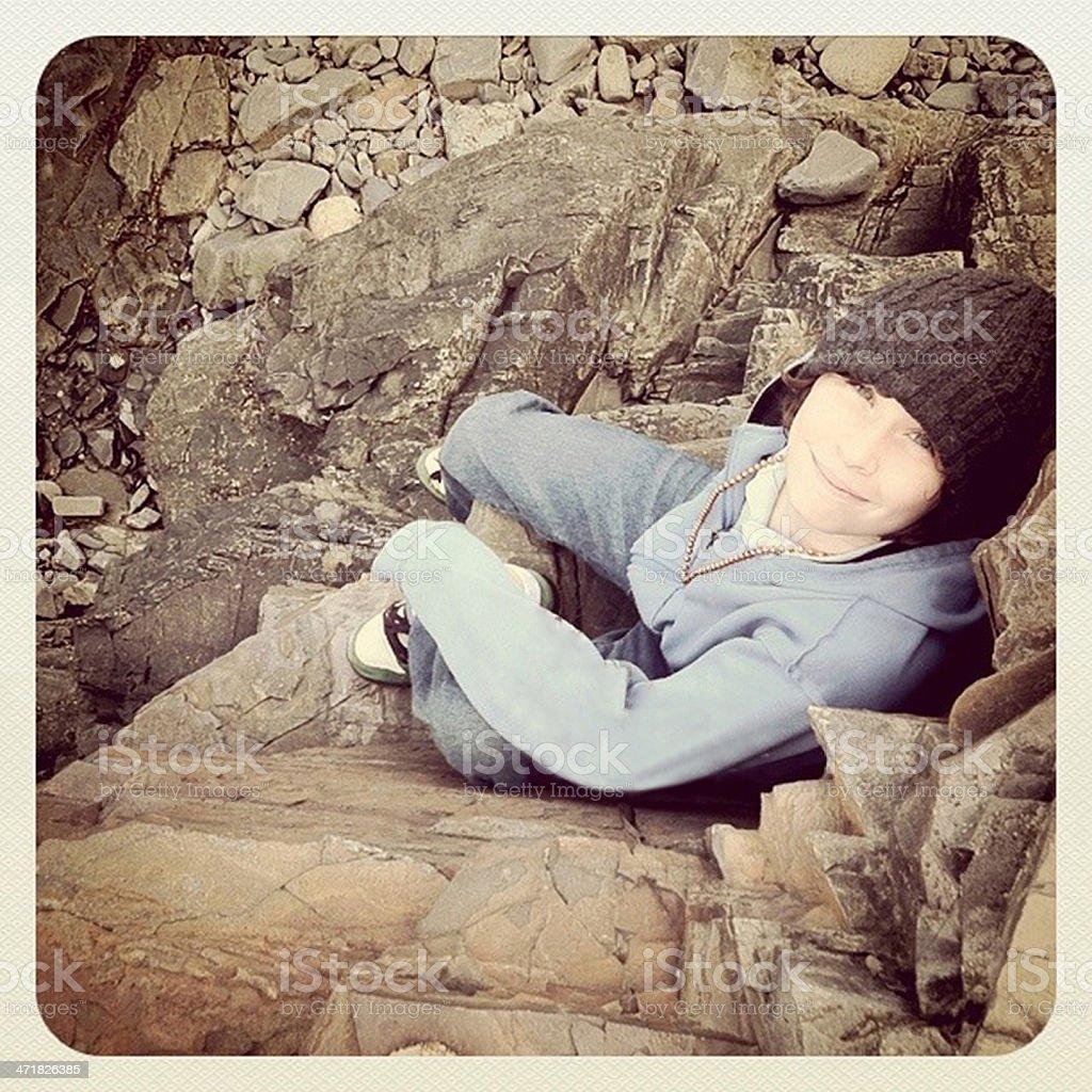 Boy Sitting on Rocks royalty-free stock photo