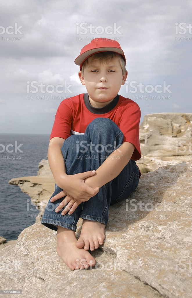 Boy sitting on rocky coastline royalty-free stock photo
