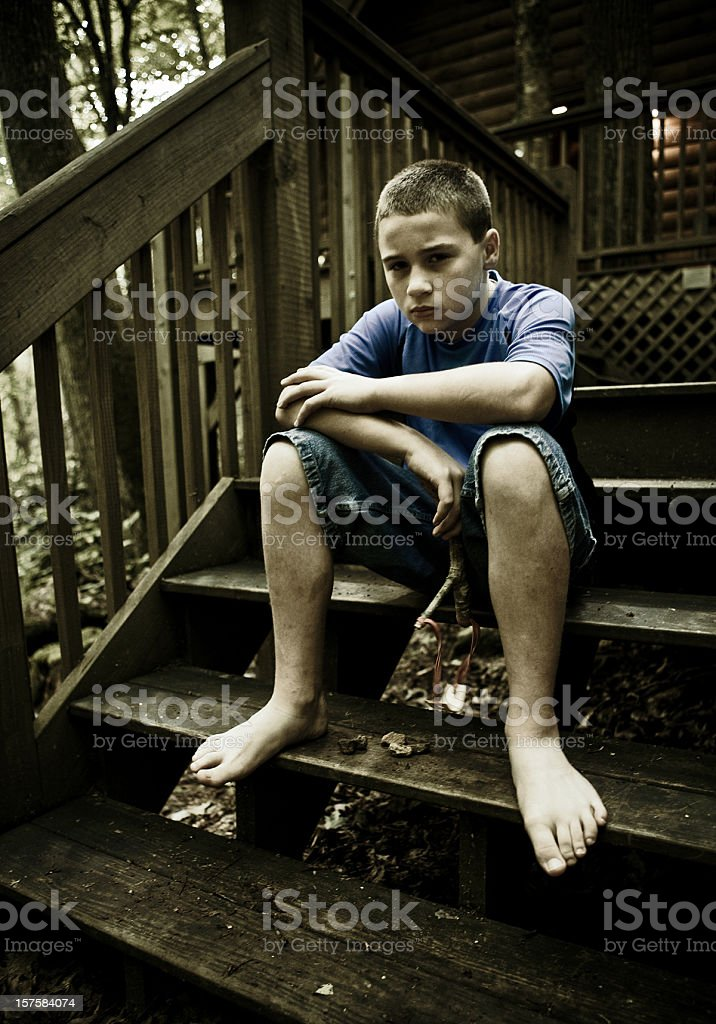 boy sitting on stairs with a slingshot stock photo