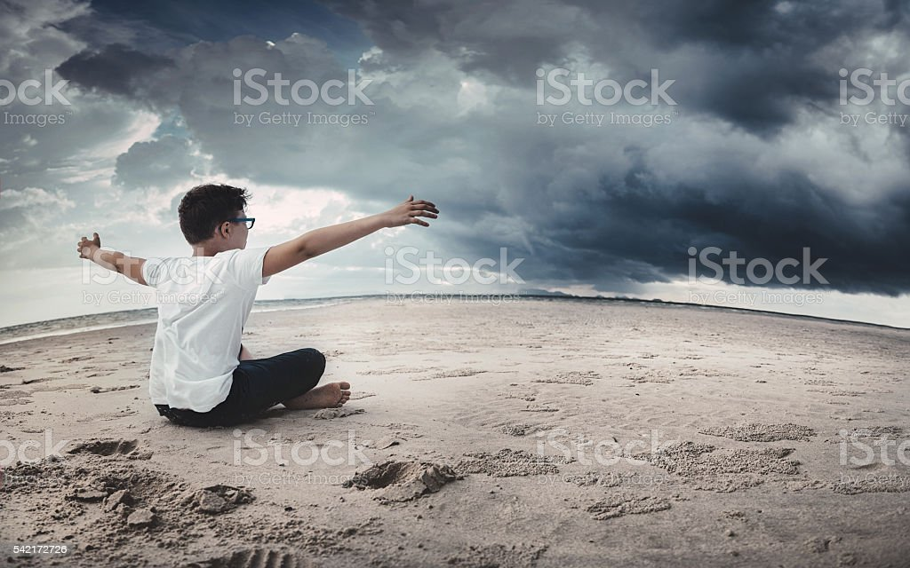 Boy sitting on the beach and looking forward stock photo