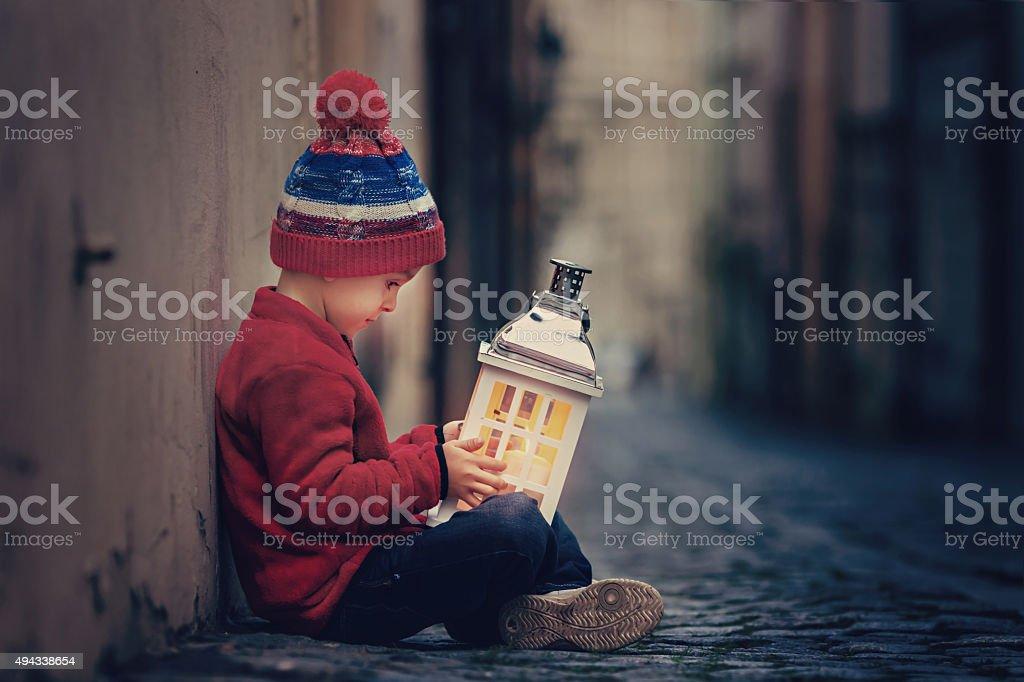 Boy, sitting on the street, holding lantern stock photo