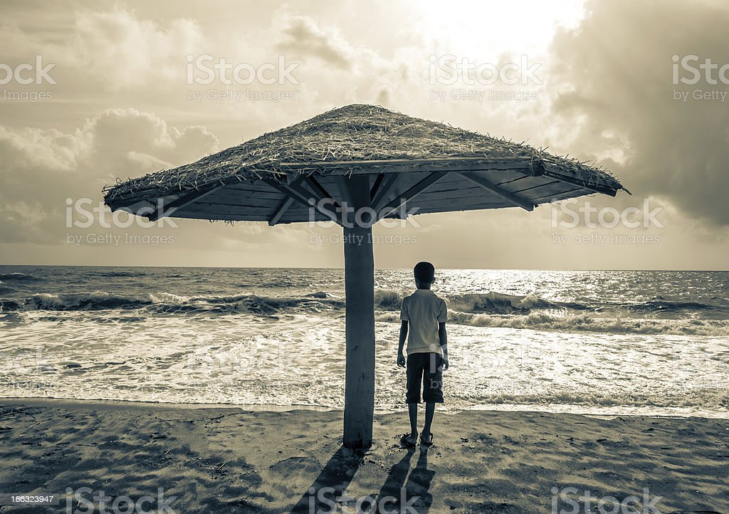 boy sitting under beach hut royalty-free stock photo