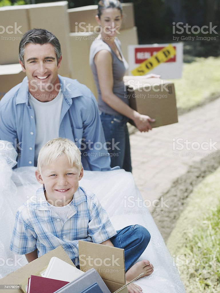 Boy sitting with books in box outdoors with man and woman carrying...
